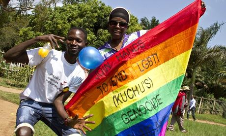 Ugandan men hold a rainbow flag reading